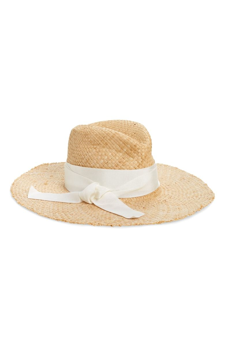 34944583ec686 A grosgrain ribbon tied in a jaunty bow wraps the crown of this  sun-shielding straw rancher hat.