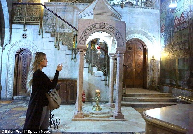 Touched: Khloe appeared humbled as she stood in front of the tomb of Jesus Christ...