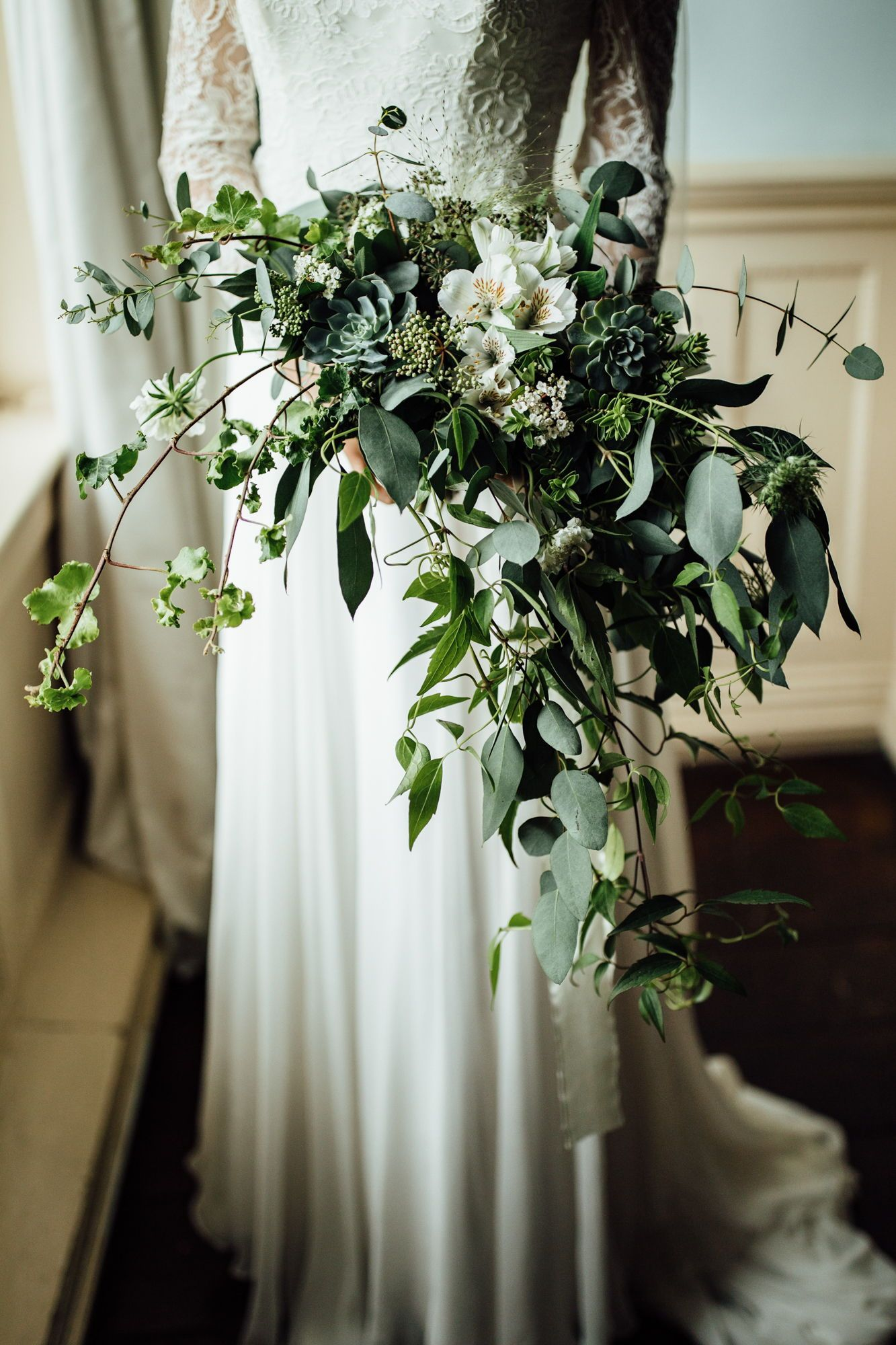 Cascading bouquet with foliage and white flowers. Winter wedding, classic green & white wedding inspiration. See the full supplier list on the blog, link below.