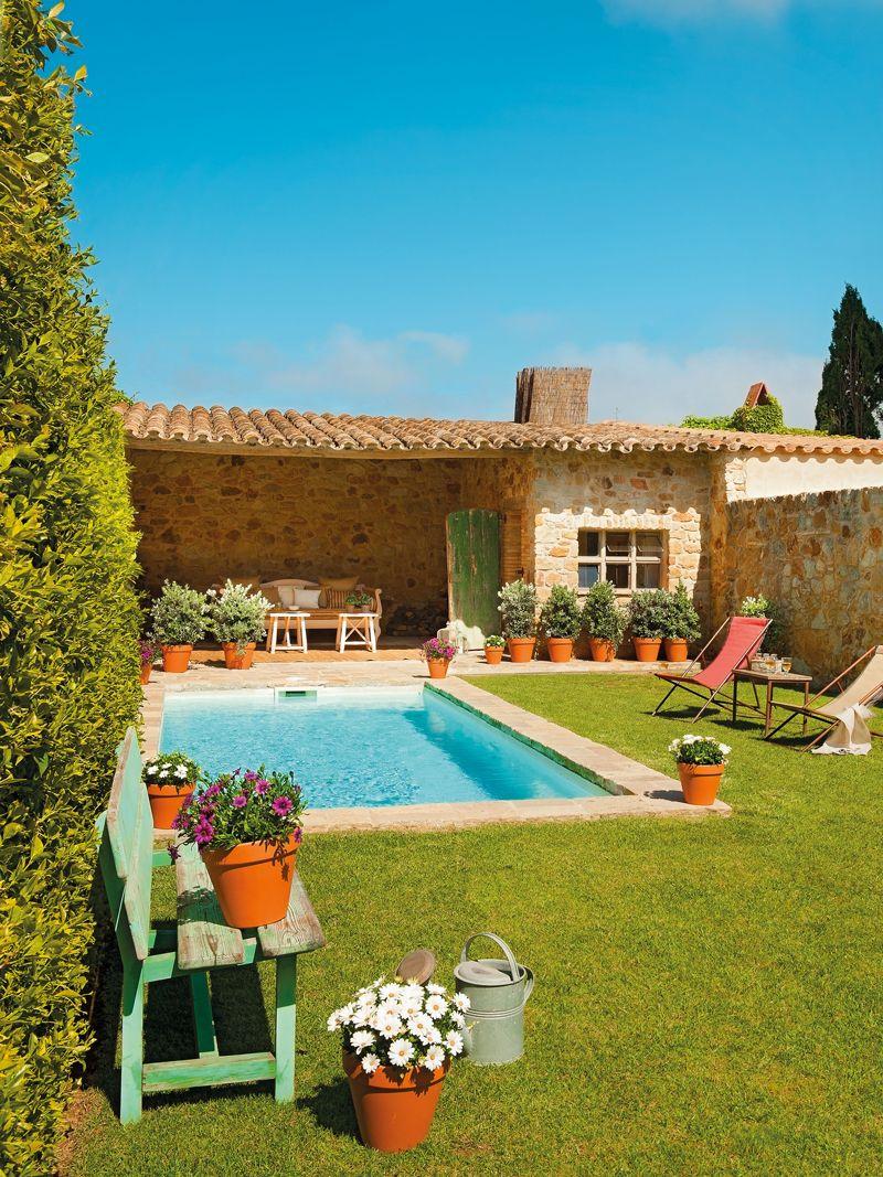 Piscina desbordante de una casa con fachada de piedra for Piscinas en el campo