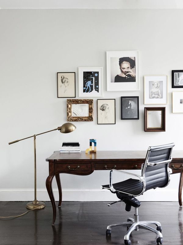 Workspace/study/home office: classic traditional mahogany wooden desk with drawers, gold floor lamp, dark timber floorboards, black Eames Aluminium Group Management Chair, gallery with mismatched art and pictures frames over desk