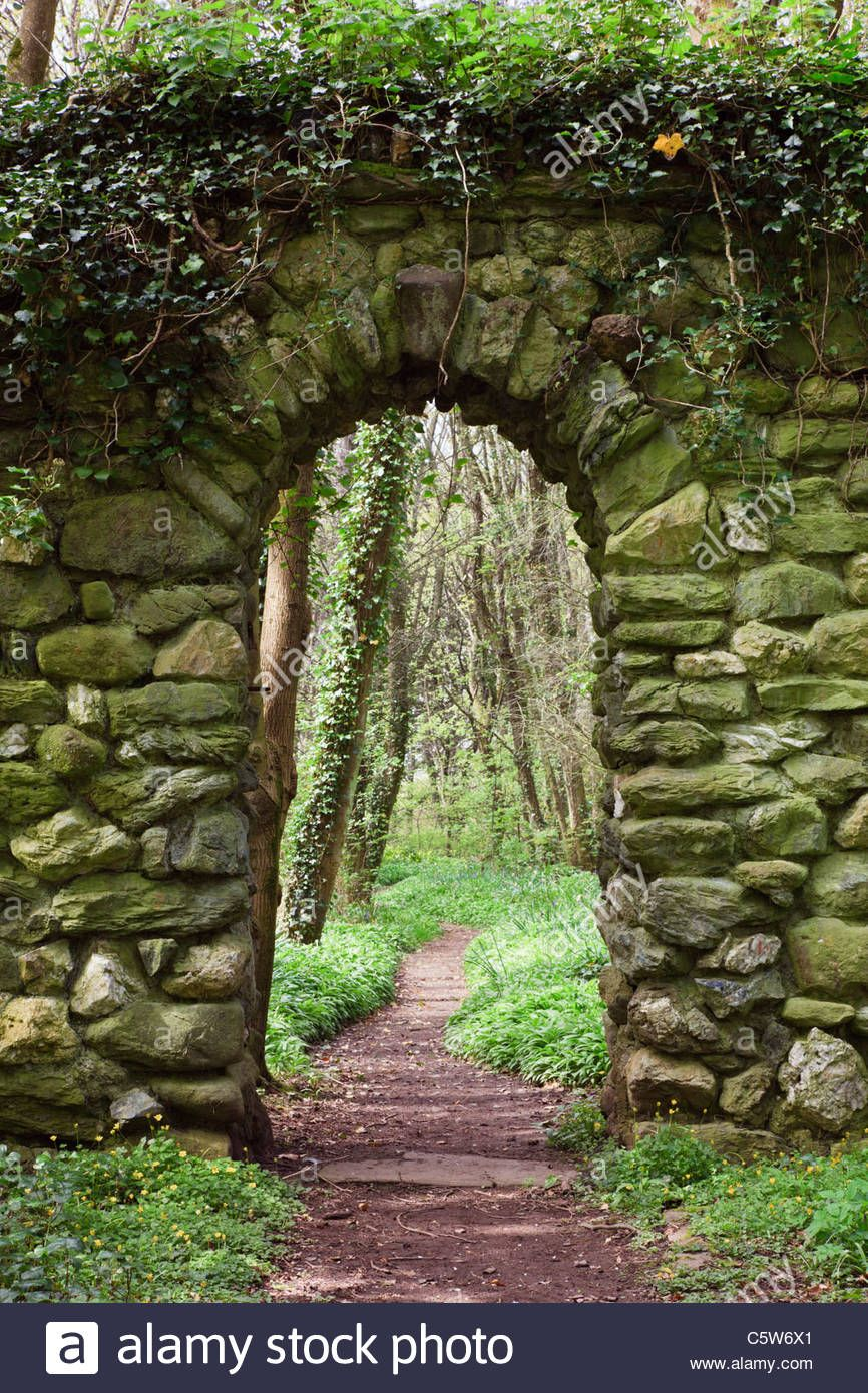 Download this stock image Stone wall arch over a garden