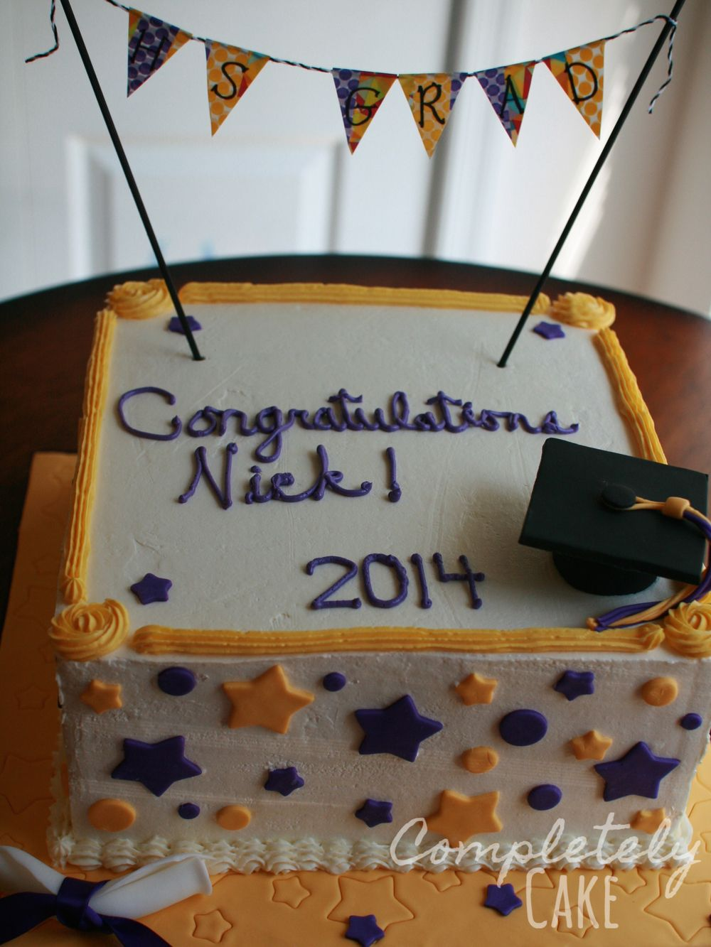 purple and yellow high school graduation cake covered with