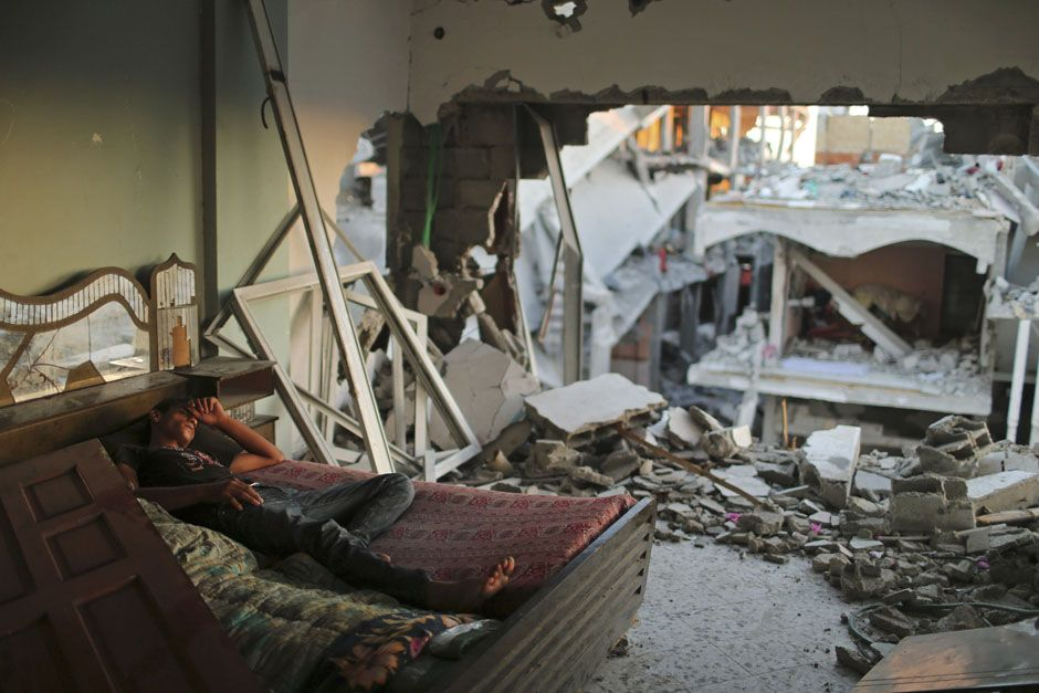 A Palestinian youth sleeps in his damaged house, with the ruins of neighboring houses visible through a destroyed portion of his wall, in Beit Hanoun town in the northern Gaza Strip September 7, 2014. REUTERS/Mohammed Salem