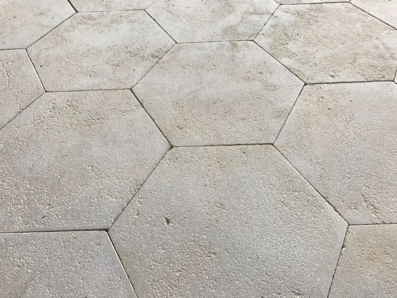 Antiqued limestone hexagon tiling with a deliberately worn surface