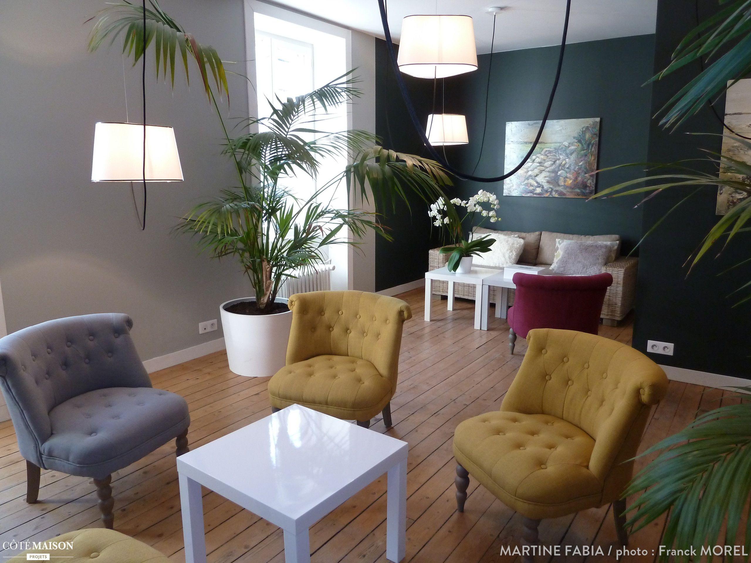 Salon avec une déco tropicale parquet en bois et fauteuil