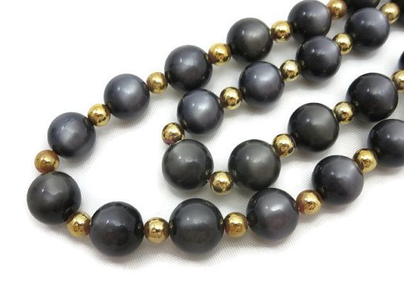A vintage moonglow lucite beaded necklace in a dark grey color with gold tone accent beads. The lucite is called moonglow because it appears to be