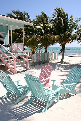 Beach chairs in cotton candy colours on white sand. Click here to shop the new Matthew Williamson holiday collection.