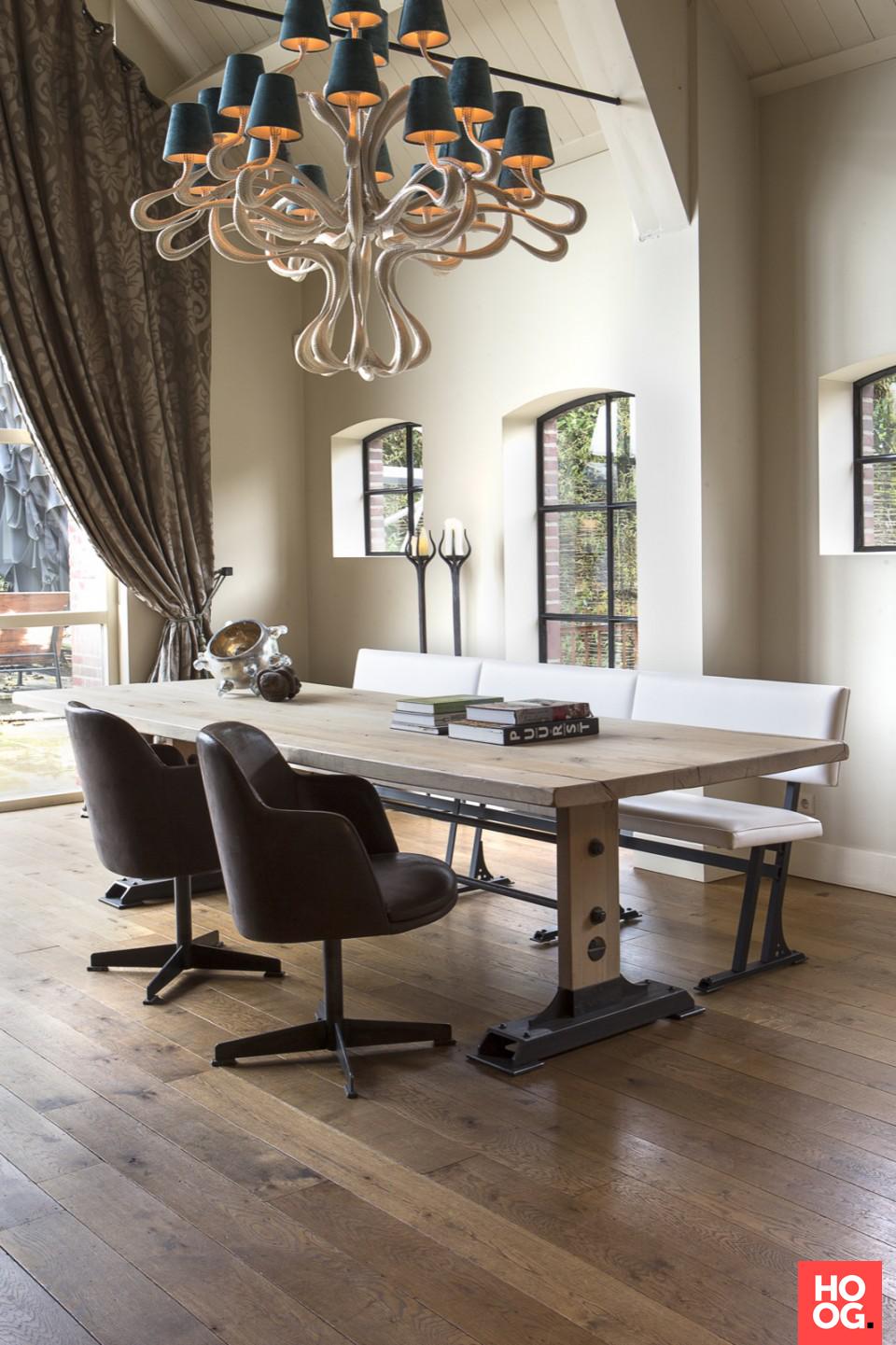 Houten eettafel met designstoelen en bank bij open haard | eetkamer ...