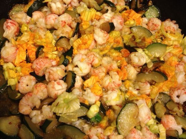 Rock Shrimp + home grown zucchini and zucchini blossoms. Served over fresh fettucine. sautee garlic and red pepper flakes in olive oil, add sliced zucchini and cook until partly caramelized. Add thawed Rock shrimp (Trader Joe) combine well add 2 pats salted butter, at the very end add sliced raw zucchini blossoms. Serve with Egg Fettucine (Buitoni) and finish with EVOO