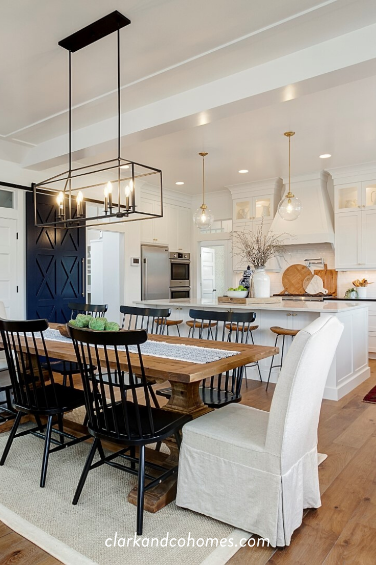 The dining room connects seamlessly to the kitchen in this custom modern farmhouse designed and built by Clark & Co. Homes in Boise, Idaho. A custom X-design barn door hides the butlers pantry from view while adding decorative elements to the open concept space. #customhome #diningroomdecor #kitcheninspiration