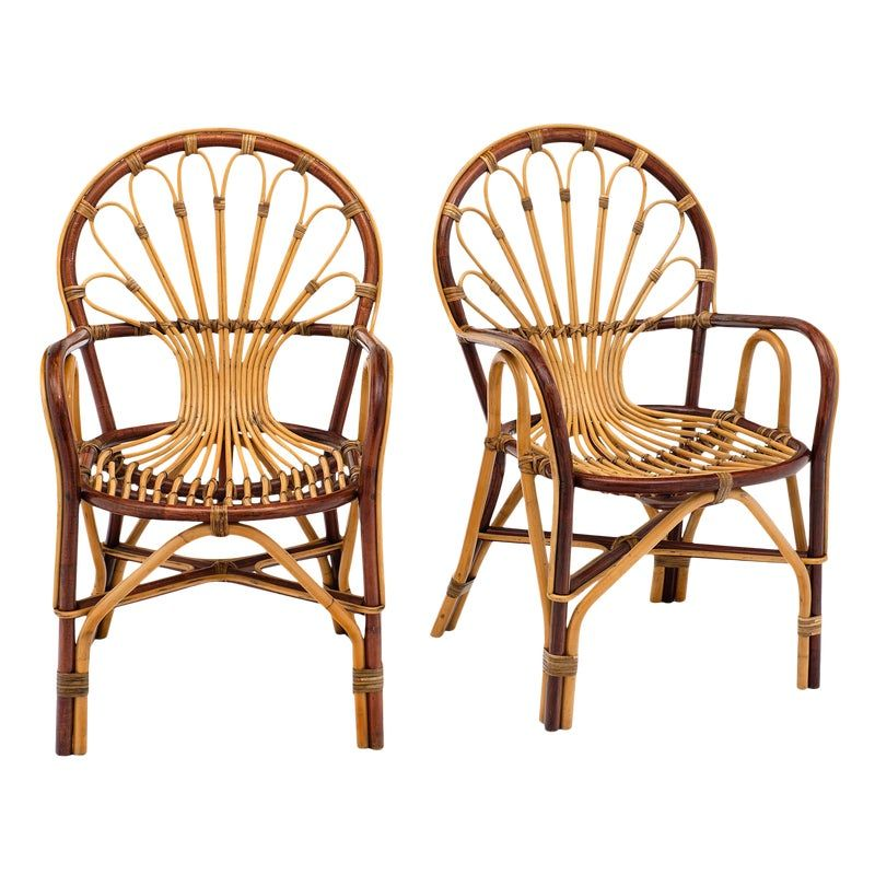 French Rattan mid-century armchairs with the beautiful sun design on the back from the 1950s. These beautiful sun-batch chairs were used as outdoor pieces near baths and has a rich patina.