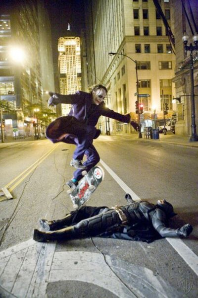 """Heath Ledger as the Joker, skate boarding over Christian Bale as Batman while they take a break on the set of The Dark Knight"""