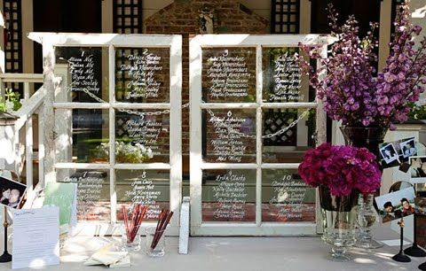 table numbers and seat assignments are written on glass panes of old window