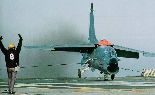 A French Navy F-8 Crusader catches the arrester cable on a carrier.