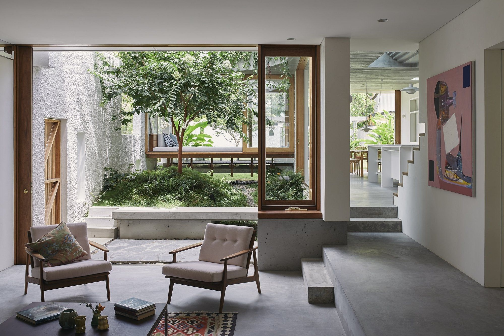 Photo of Breezy open air living spaces centered around a small courtyard garden with a kitchen opening…
