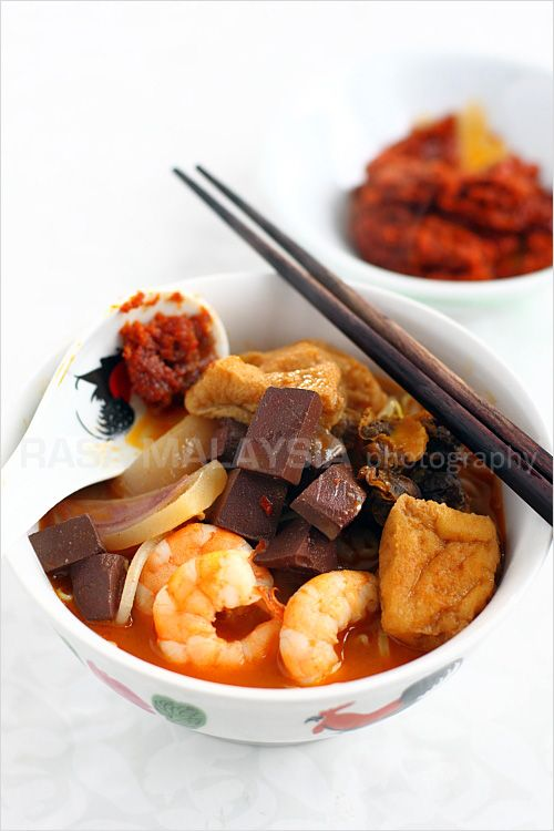 Penang Curry Mee recipe - There are many variations in Malaysia, with toppings many would consider bizarre: pig's blood cubes (they taste like tofu except that they are maroon in color), bloody cockles, soaked cuttlefish slices, shrimp, and tofu puffs. I am a firm believer that these ingredients are the souls of Penang curry mee, without them, it's not quite the same. #curry #malaysian