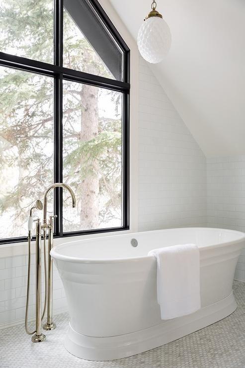 A White Glass Beehive Light Pendant Hangs Over An Oval Freestanding Bathtub With A Floor Mount Gooseneck T Free Standing Bath Tub Bathtub Transitional Bathroom