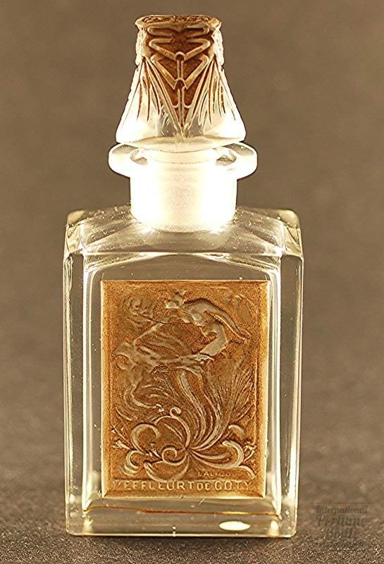 L'Effeurt, Coty, Perfume bottle, Glass with brown patina, Rene Lalique, France, Perfume registered in 1908; this flacon in 1912, 11 cm. Lalique's first work in glass for Coty was the design of this image (1908) on the face of this bottle without the markings below. These glass labels were affixed to a traditional Baccarat bottle when the glass was at the proper temperature. When Lalique acquired his own glassworks he designed a new flacon for this perfume, seen here.