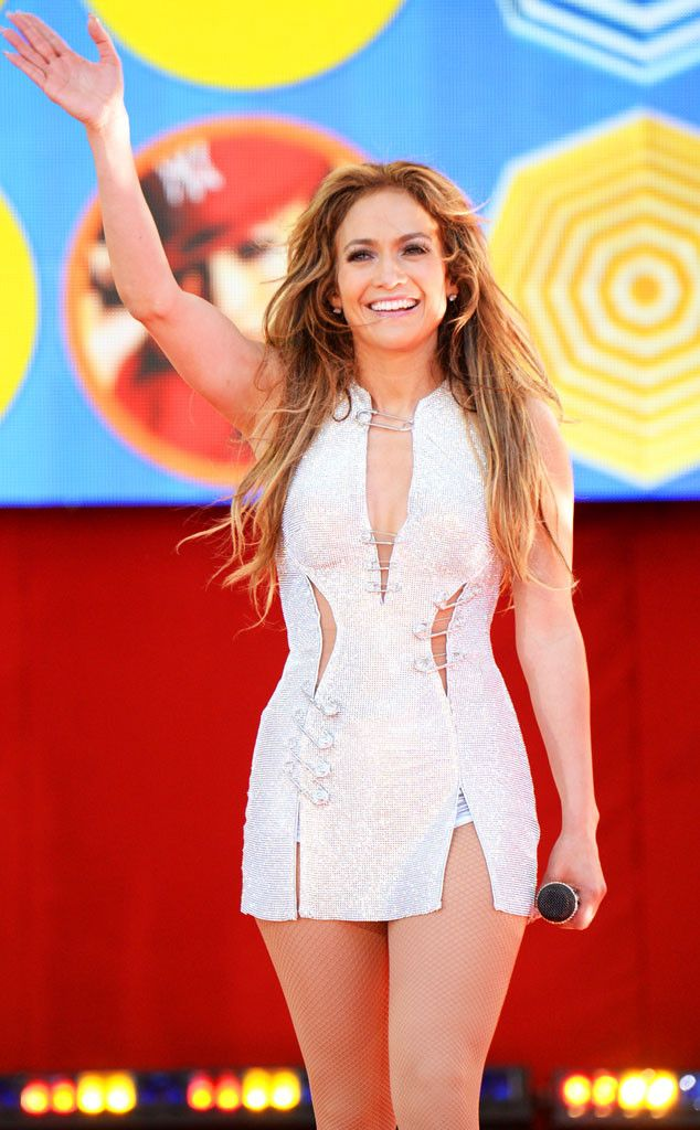 Jennifer Lopez is all smiles as she performs in a sparkly dress held together by safety pins.
