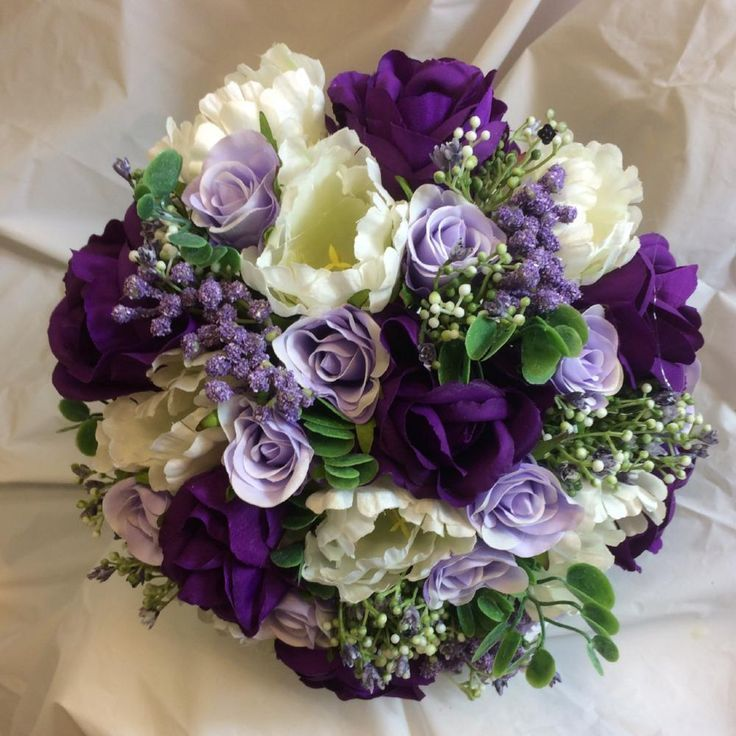 A brides bouquet of purple, lilac and ivory silk roses & tulips
