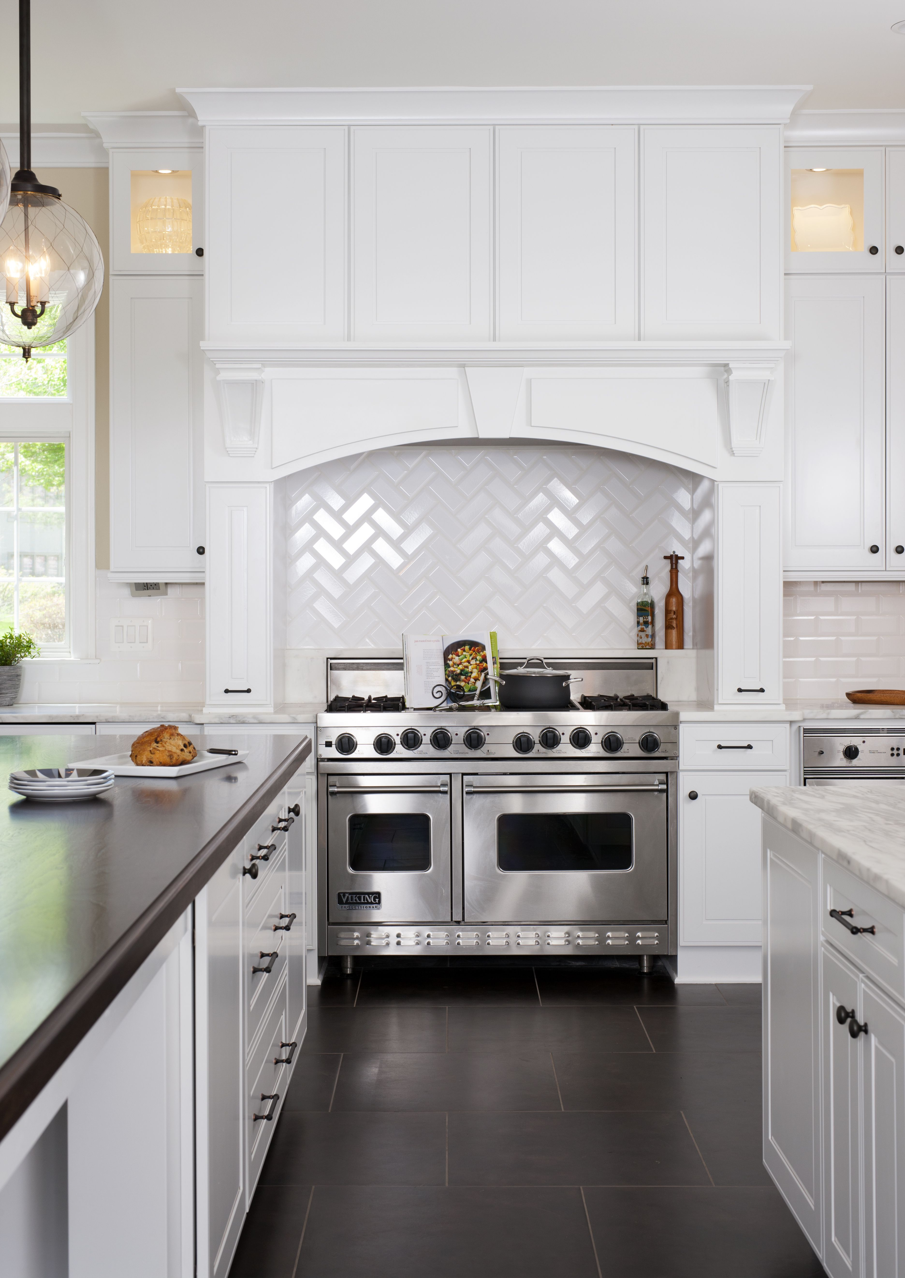 A classic white kitchen featuring Calacatta marble countertops and ...