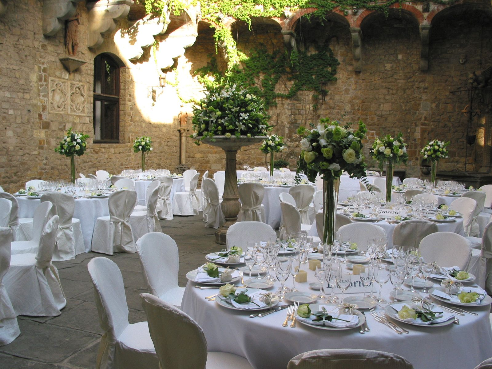 Tall glass vases with white flowers and greenery. Event Planner : Blanc Ricevimenti.