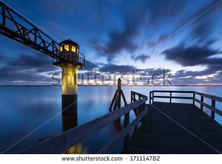 Dock pole and lighthouse at sunrise at Lauwersmeer by Marcel Kerkhof, via Shutterstock