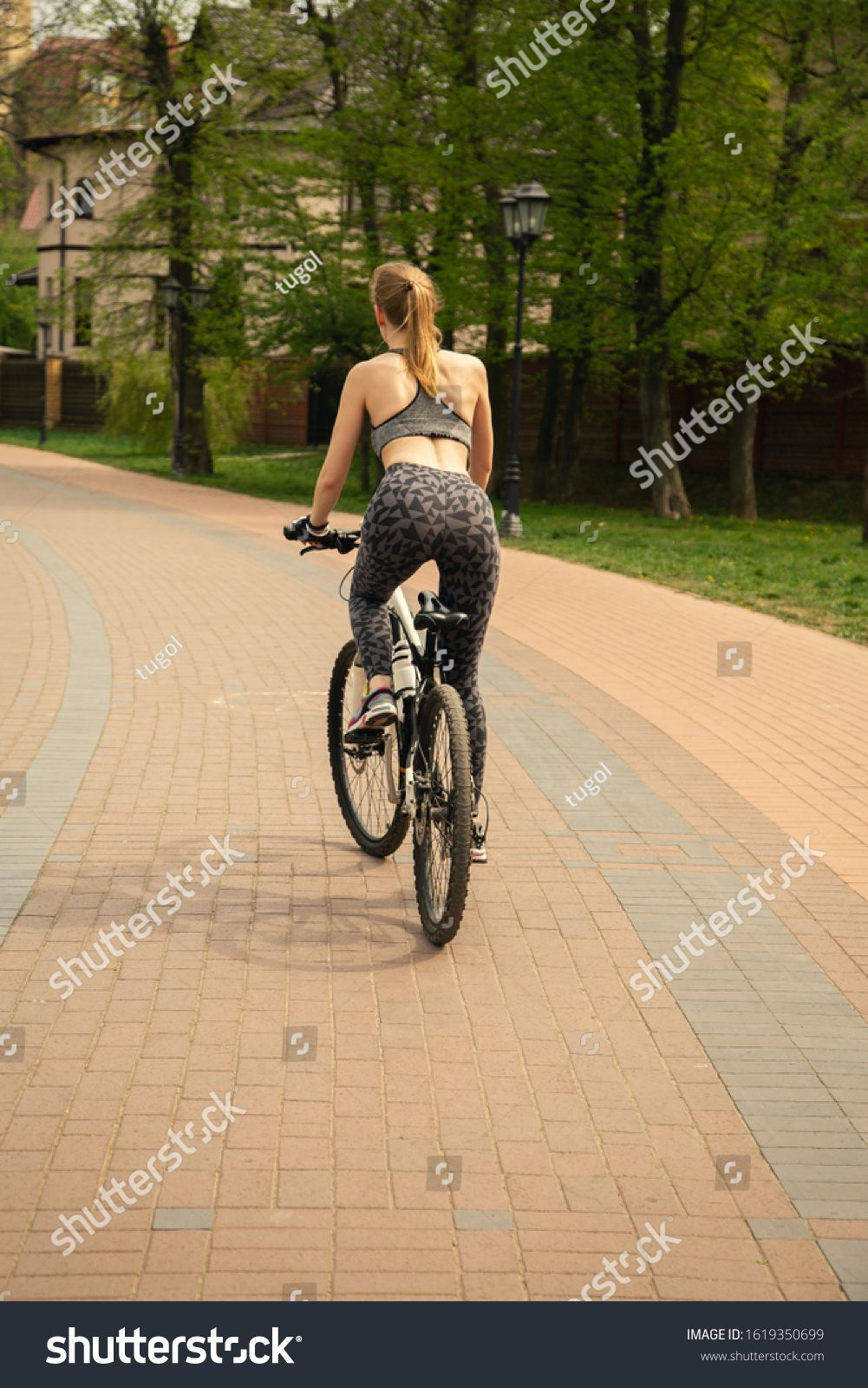 sports slim young blond woman move on bike in park Ad ,