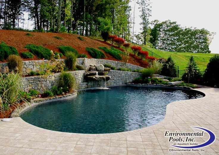 Free form pool built into hill with artistic paver decking for Pool design hillside