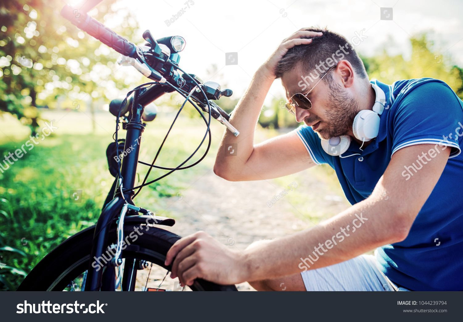 Man checking the tire during the bike ride in the park. Sport and recreation concept ,