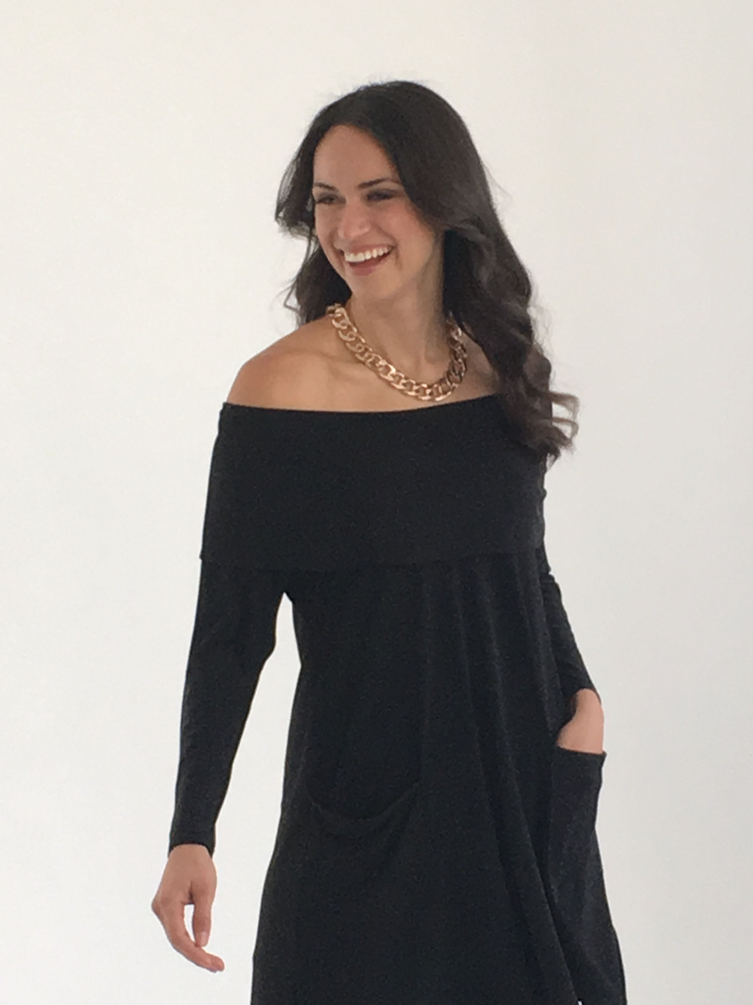 The Off-the-Shoulder Tunic in Black  Even if you like to cover your arms, like I do, you can still enjoy an off-the-shoulder look. This tunic has shape, and like all of our tops is very figure flattering. Grazes over your hips, mid-thigh length with slits.  Elastic holds comfortably around your upper arm and doesn't feel like it's going to fall. Can also be worn as a cowl neck.  A drape pocket is the perfect dot on the i! Looks FAB day or night.