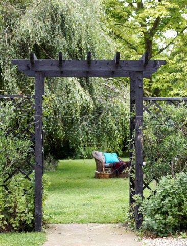 View Through Wooden Archway To Outdoor Seating In Lawned Garden