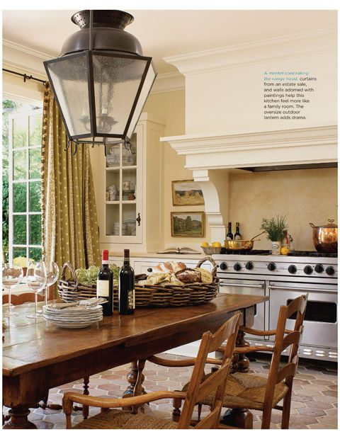 large hood over the range / oven; large table / eat-in kitchen; natural light; doors that open to the outside; large lantern