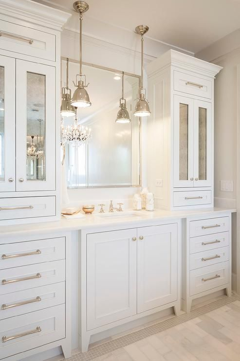 All White Bathroom Features An Extra Wide Single Vanity Topped With Marble Under A Polished Nickel Mirror Illuminated By Mini Yoke Pendants Flanked