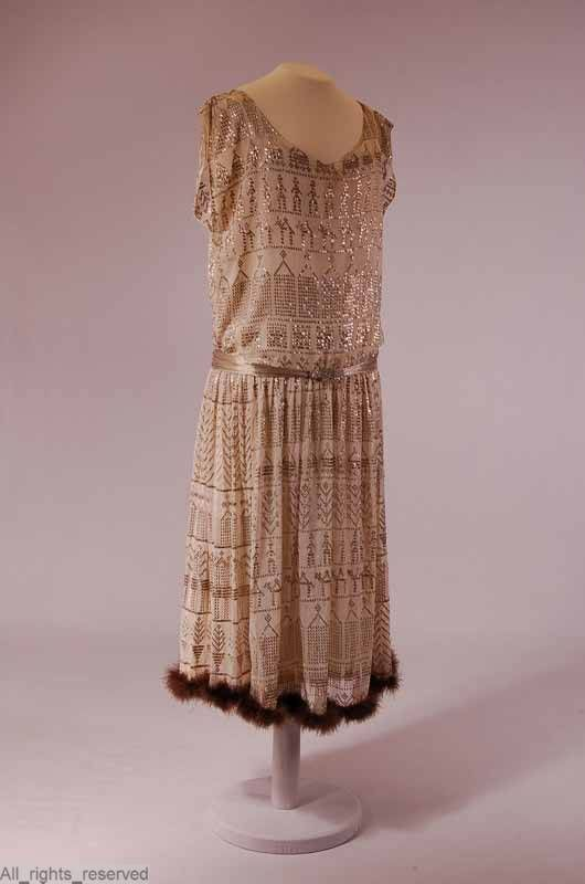 The frock is from 2 egyptian shawls made; two jobs are the bodice and the skirt four jobs. cotton white tulle; decorated with silver thread (originally egyptian shawl); garnish: downy feathers, feather light brown fur