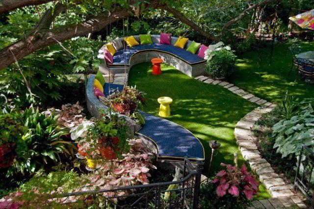 Gartenideen geschwungene Sitzbank aus Beton-farbenfrohe dekokissen