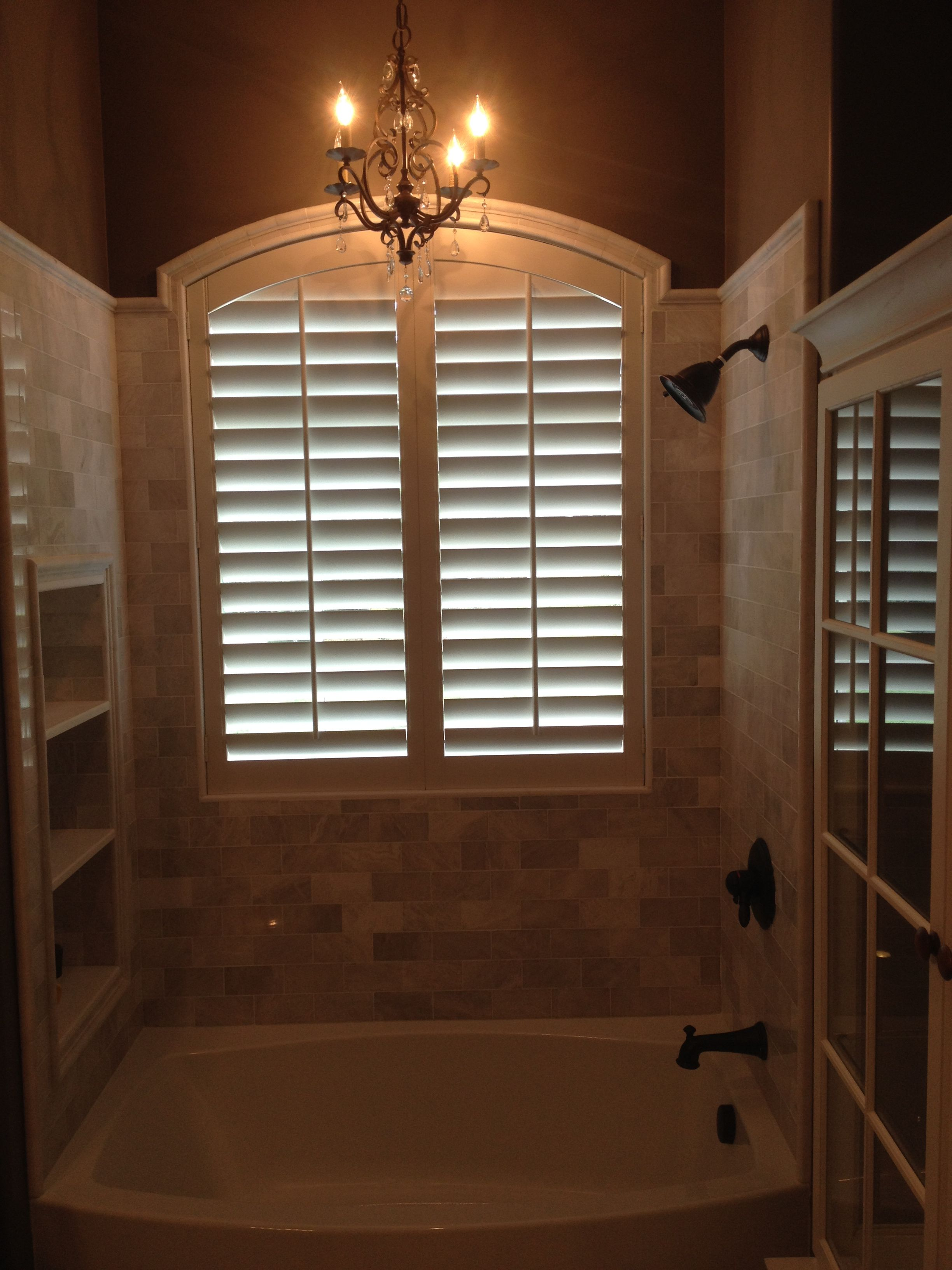 Arched plantation shutters over a bathtub these are made of our