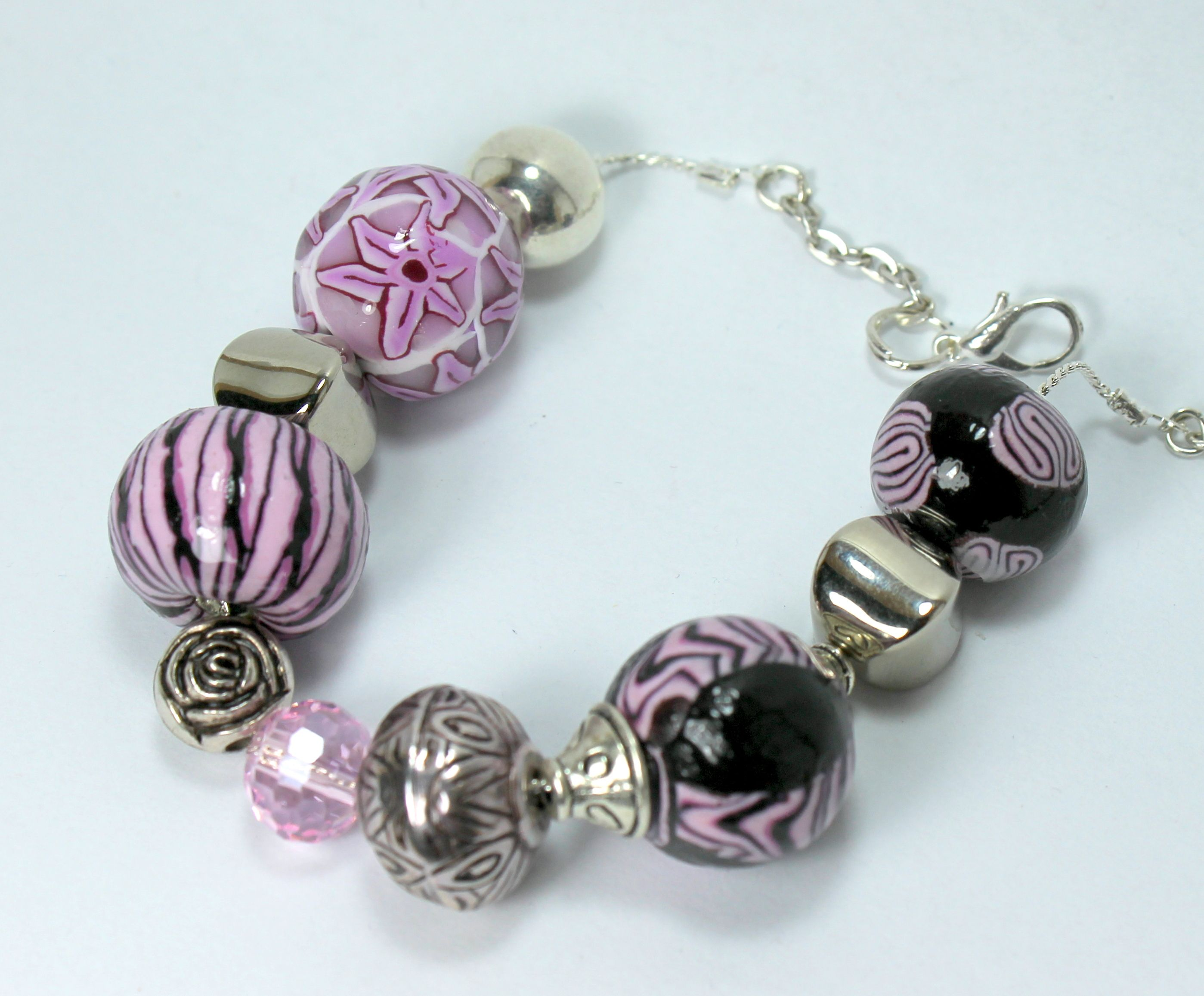 Pandora style bracelet in shades of pink , made with beads handmade in polymer clay and resin , swarovski crystal and nickel free metal components . The bracelet is adjustable with a lobster clasp closure . All material is non-allergenic . one piece