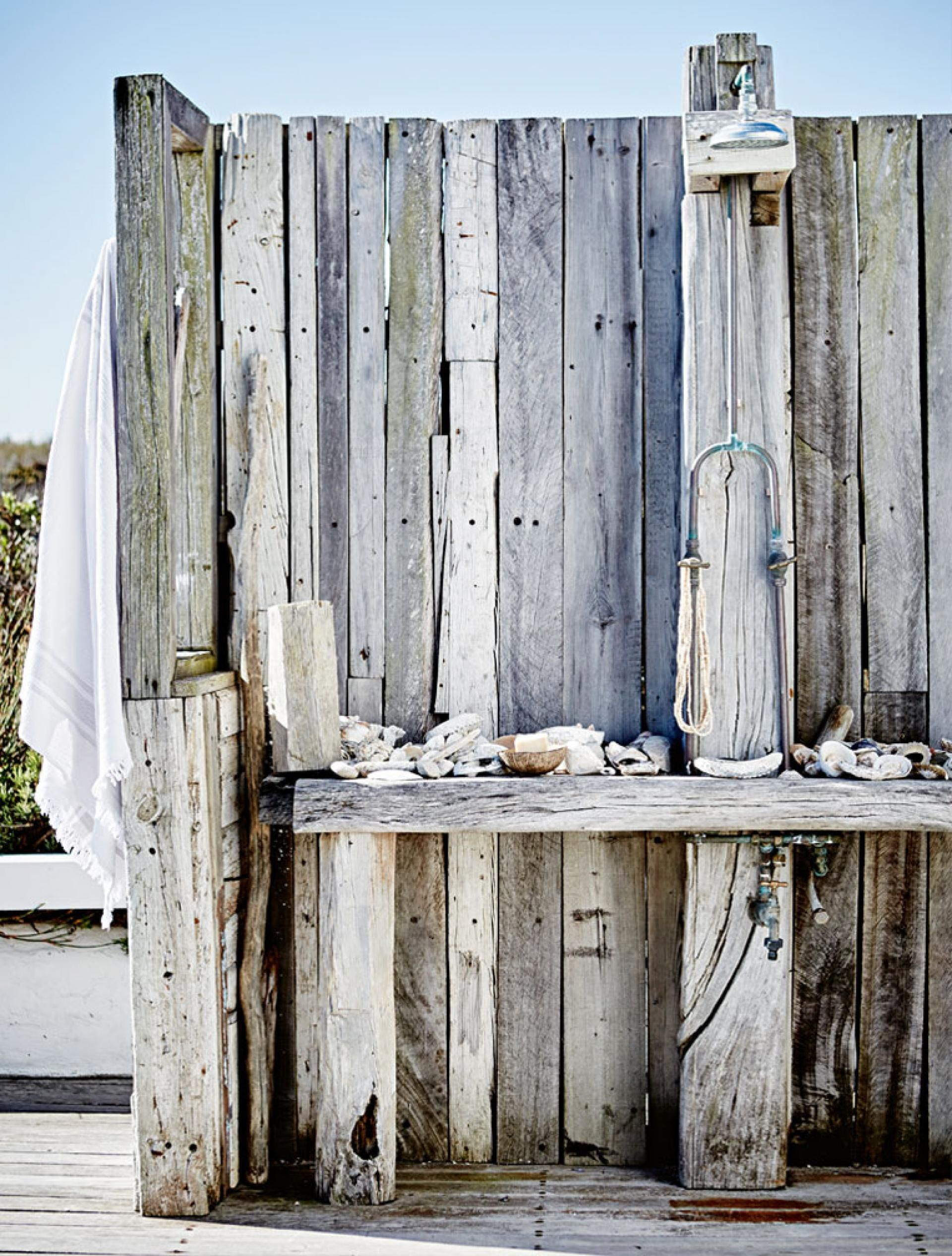The outdoor shower of a coastal home in South Africa from the December 2015 issue of Inside Out magazine. Production by Sven Alberding/bureaux.co.za. Photography by Warren Heath/bureaux.co.za. Available from newsagents, Zinio, www.zinio.com, Google Play, play.google.com/..., Apple's Newsstand, itunes.apple.com/... and Nook.