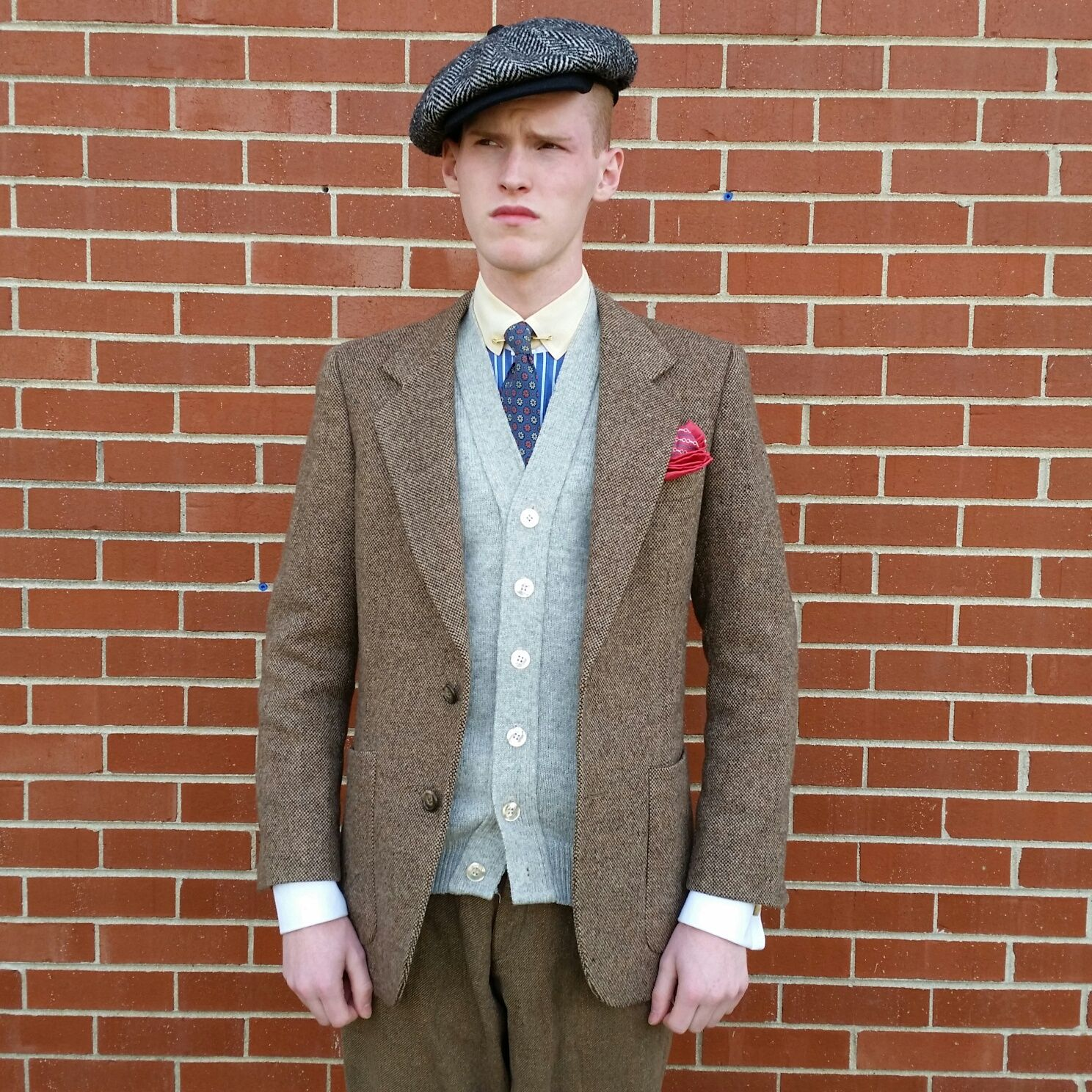 Closer view of the jacket, sweater, and flat cap. Shirt is blue cotton with white and blue stripes, as well as white French cuffs.