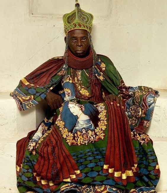 Nigerian chief wearing a garment made of a fabric bearing a huge central portrait of HRH Queen Elizabeth. Robes of office: HRM Agbogidi Obi James Ikechukwu Anyasi II, 'The Obi of the Idumuje Unor Kingdom'  Courtesy George Osodi