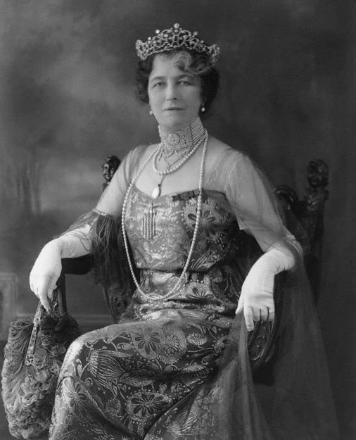 A diamond and natural pearl belle epoque tiara, circa 1900, worn here by Lady Alice Ludlow, nee Sedgewick. The tiara features open-work foliate scrolls, with interlocking garlands between three diamond motifs, topped with natural pearls.