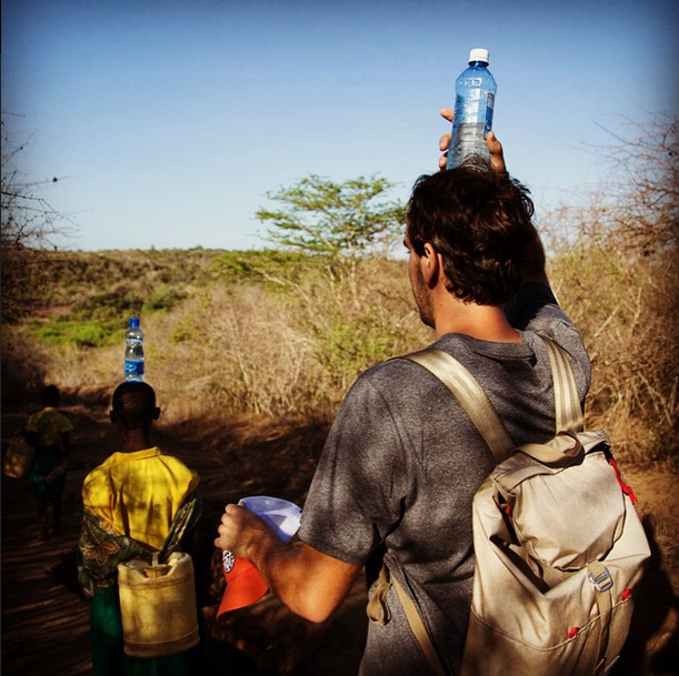 "April 7, 2015:""Mark Visser balances a water bottle on his head as he follows Neema to the swamp where her family used gather drinking water in Makumba village, Kenya. Now, she and her sister get safe water just down the road from their house."" Photo by Chris Huber"