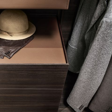 drawer units in coal larch melamine finish with top in regenerated castoro leather. The cloth hanger rods are also available with regenerated castoro leather.