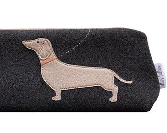 Wool felt appliquéd Dachshund in stone on a charcoal grey melton background with a coordinating zip and side tab.  The purse is lined in a