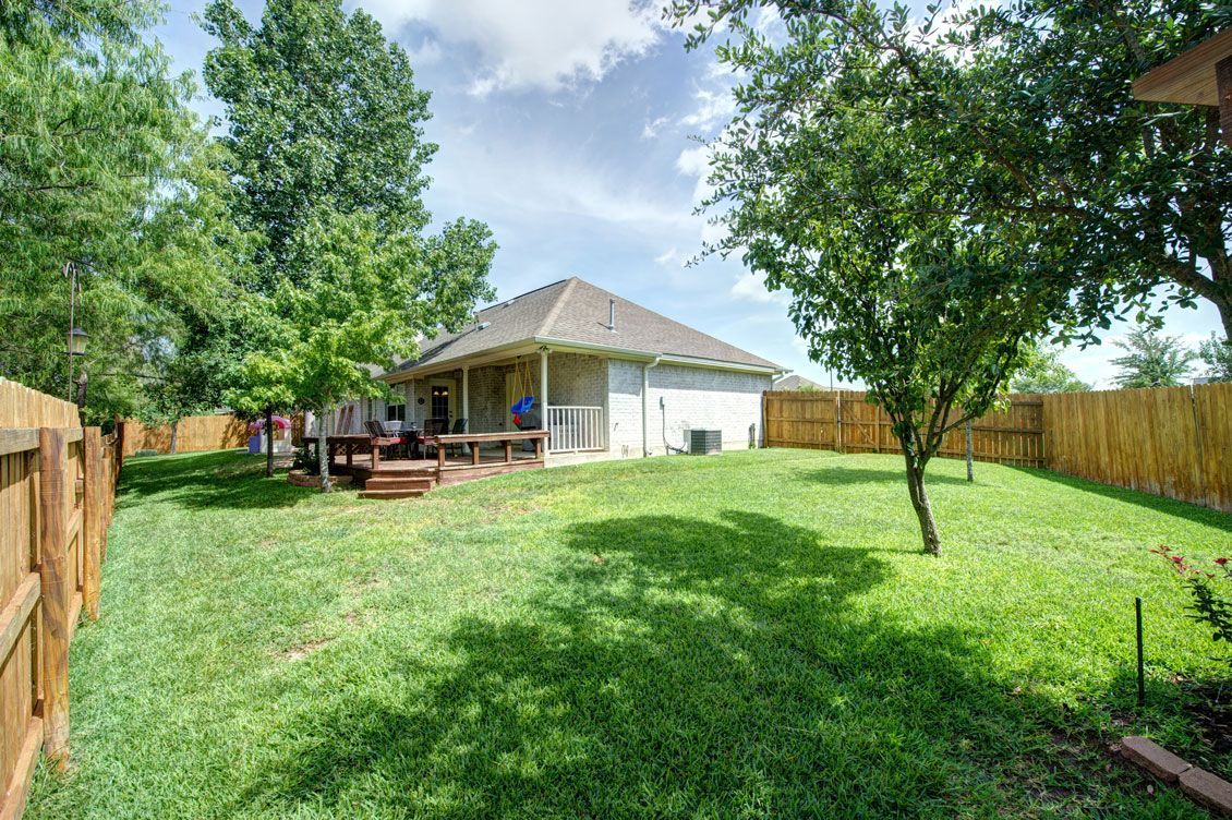 the large backyard features a covered porch wooden deck and