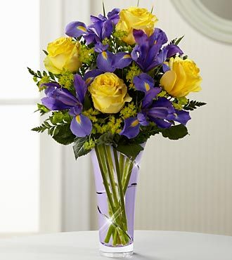 Yellow Roses And Irises Note Colored Water In Vase Yellow Flower Arrangements Iris Bouquet