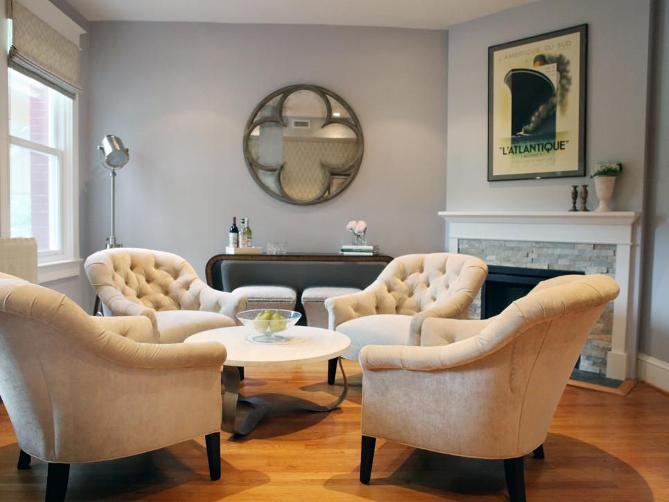 In this transitional living room, a quartet of tufted armchairs