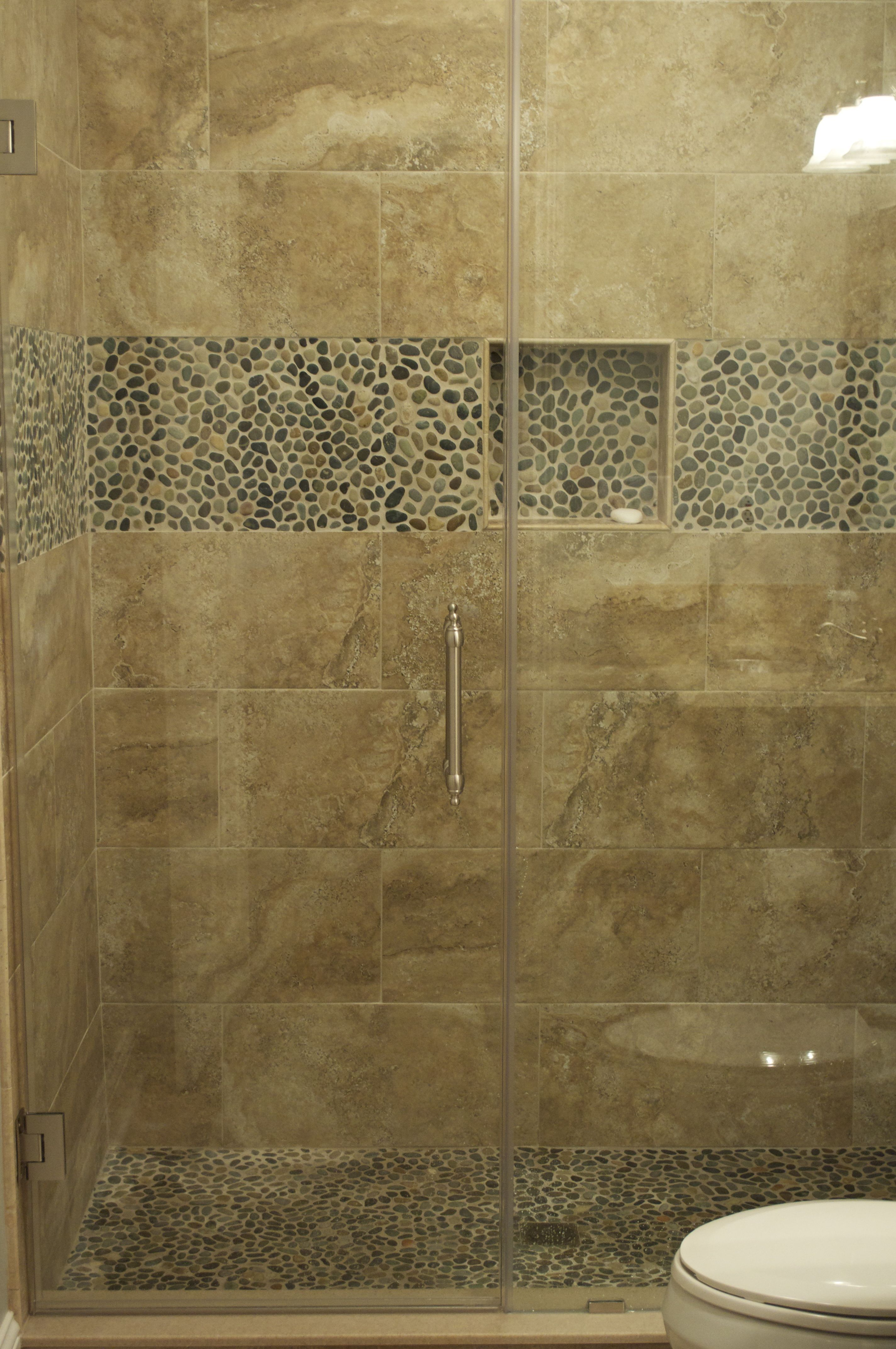 CMH Builders Custom tiled shower with pebble floor, border, and shampoos niche